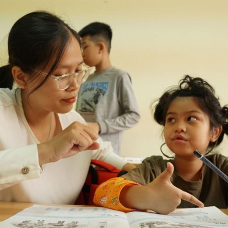 La maestra Ngoc Anh enseña a Nguyen Ngoc Bao Chau, de 7 años, durante una clase de vietnamita. Fotografía: Le Thang/Banco Mundial.
