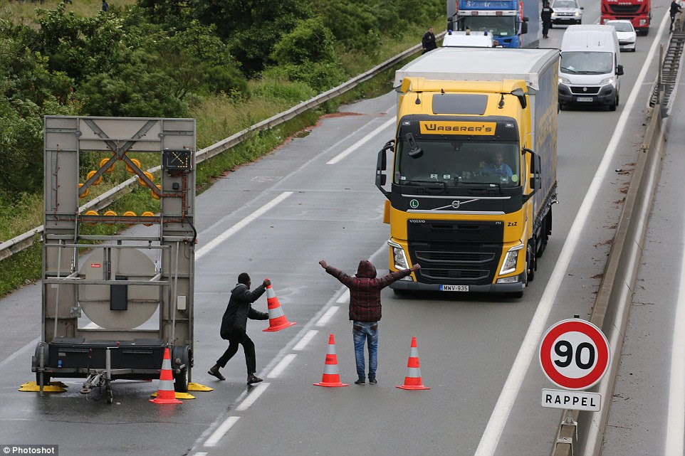 Roadblock: Two migrants run into the road and use traffic cones to force a Hungarian trucker to pull over near Calais