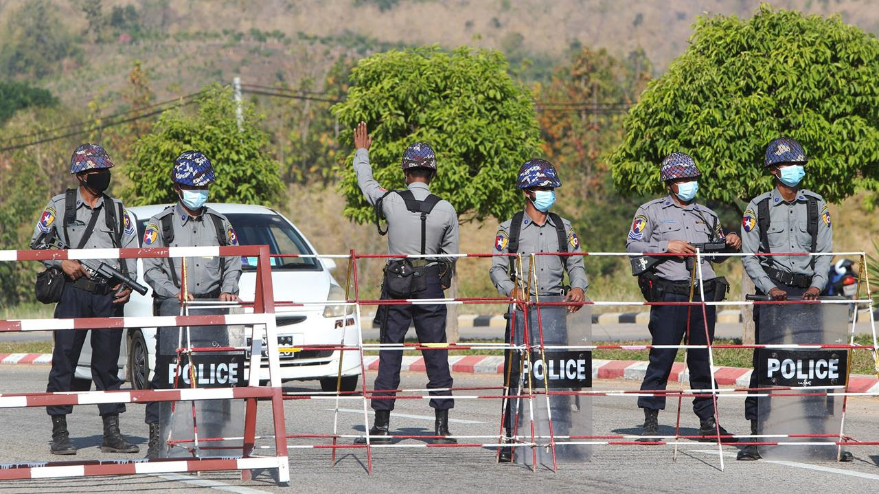 Policemen wearing protective face mask stand guard behind a road barricade, Jan. 29, 2021.