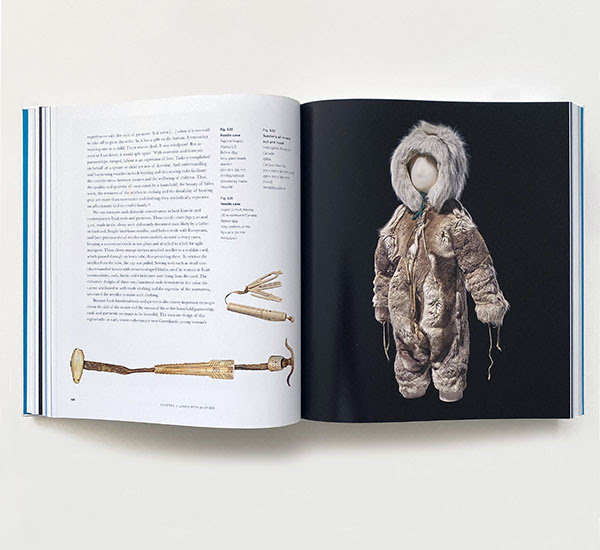 The exhibition catalogue open showing text and an image of a child's snowsuit.