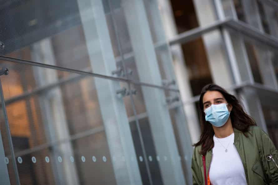 A woman wears a face mask as she walks in Manhattan, New York.
