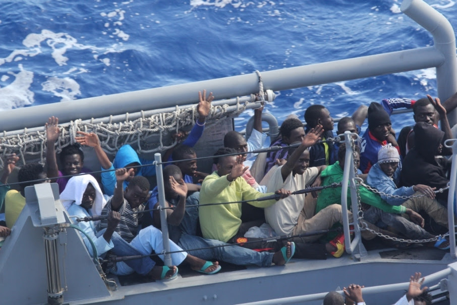Distressed persons wave after being transferred to a Maltese patrol vessel.