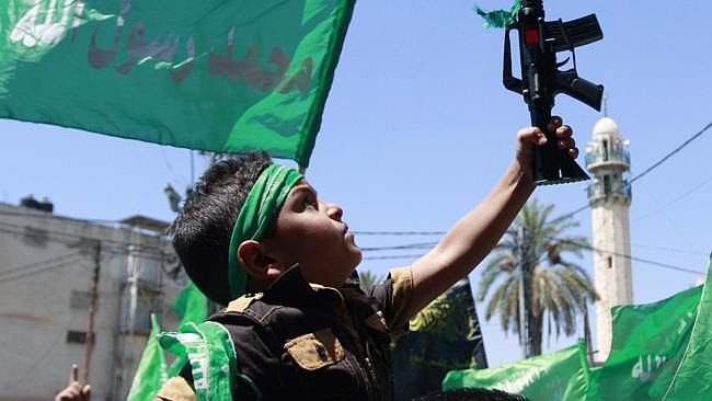 A Palestinian boy holds a toy gun as supporters of Hamas and the Islamic Jihad movement c