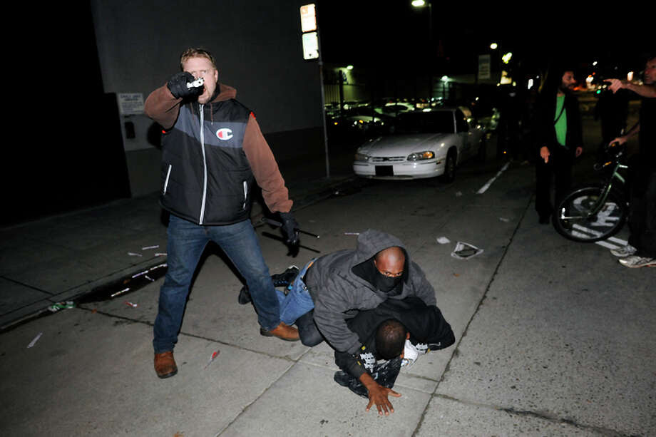 An undercover officer points his gun at the crowd while his partner subdues a protester who struck him in the back of the head, as demonstrations continue for a fifth night in Oakland on Wednesday, Dec. 10, 2014. Photo: Michael Short / Special To The Chronicle / ONLINE_YES