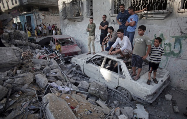 Palestinians look the damage of a destroyed house where five members of the Ghannam family were killed in an Israeli missile strike early morning in Rafah refugee camp, southern Gaza Strip.