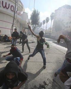 Manifestantes palestinos lanzan piedras contra soldados israelíes durante enfrentamientos en la ciudad cisjordana de Hebrón. EFE/ABED AL HASHLAMOUN