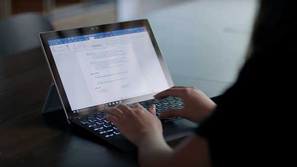 A person with a computer in their lap uses Word and Resume Assistant to draft their resume.
