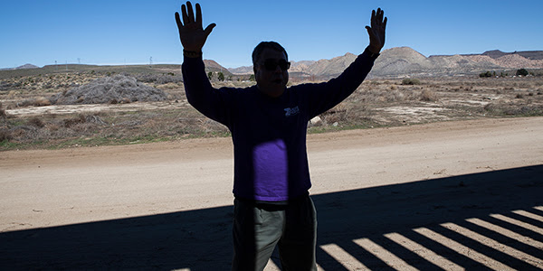 A man in the shade holding his hands up