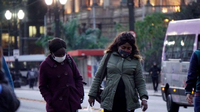Duas mulheres caminham usando máscara contra covid-19 e roupas de frio no centro de São Paulo, no fim de tarde