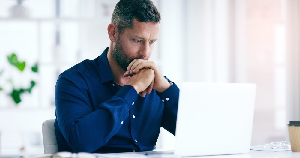 Man looking at his computer with folded hands