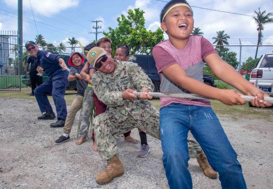 ilitary members playing tug-of-war with Micronesian children (Mass Communicat