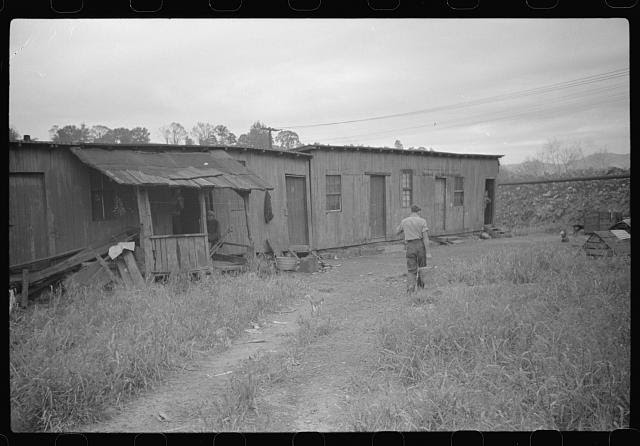 Carrying water, coal miners shacks. Scotts Run, West Virginia