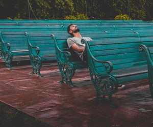 man sitting alone on bench