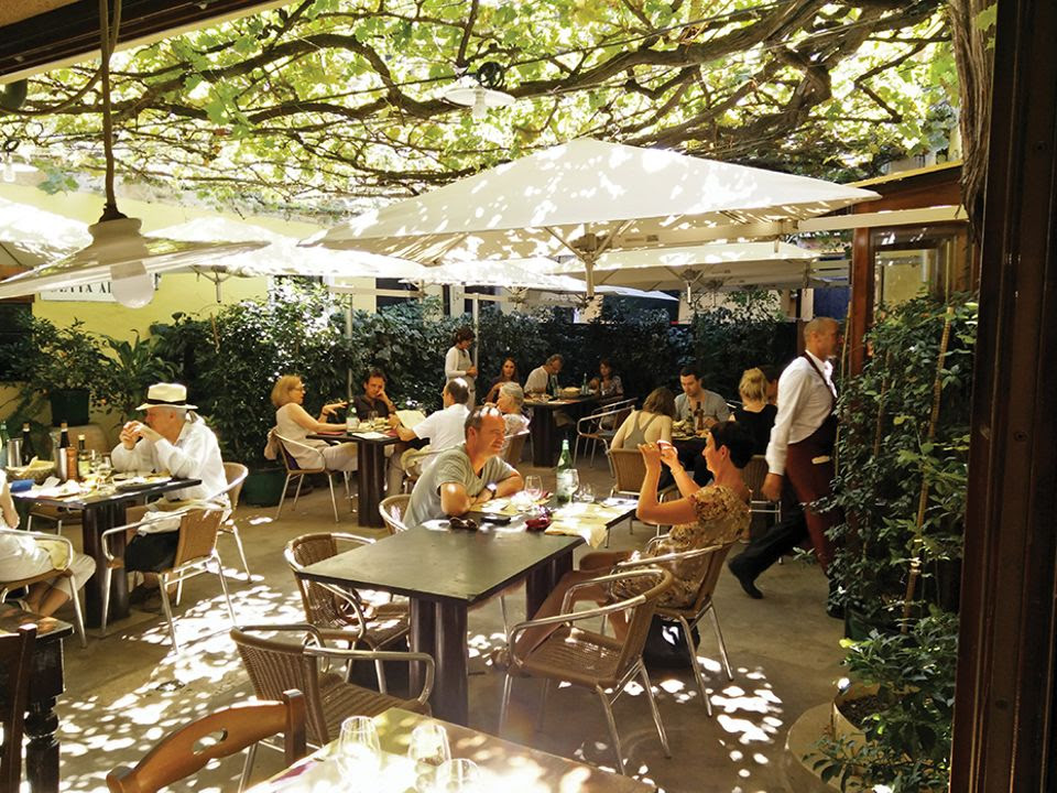 Relax in Trattoria Corte Sconta's vine-covered courtyard