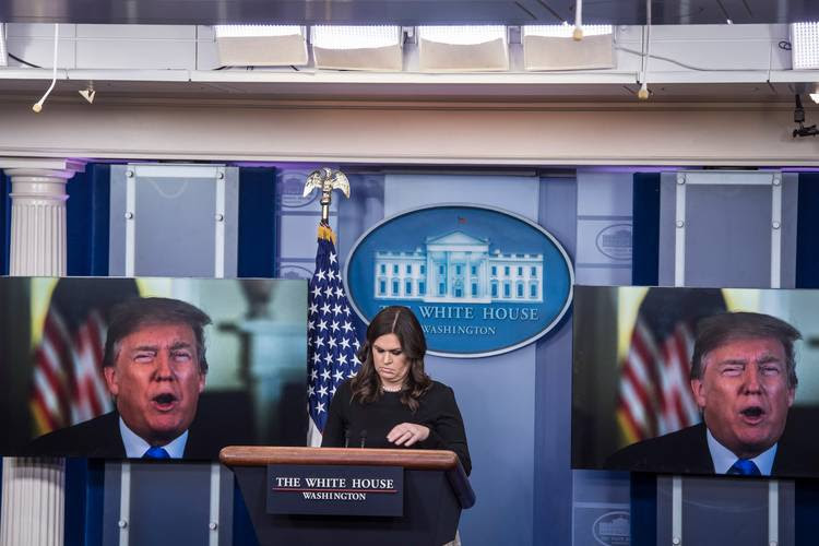A video of Trump appears on screens before Sarah Huckabee Sanders talks to reporters during the daily press briefing. (Jabin Botsford/The Washington Post)