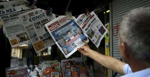 Un hombre lee en un quiosco en Atenas los periodicos del día con la noticia de la convocatoria del referendum sobre el rescate.  REUTERS/Alkis Konstantinidis