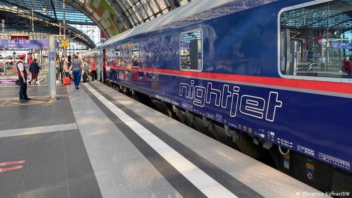Trem azul inscrito Nightjet em plataforma de estação