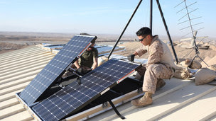 Corporal Robert G. Sutton and Corporal Moses E. Perez installing solar panel on a combat post. U.S. Marine Corps/Lance Cpl. Alexander Quiles via REUTERS