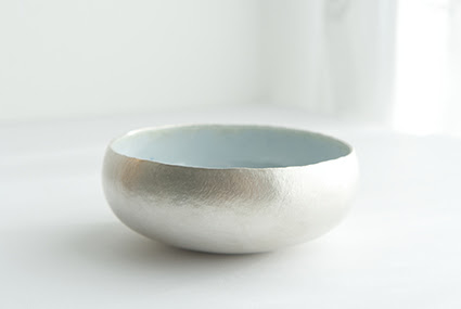 A photograph of a silver and enamel bowl by Emma Louise Wilson. It is displayed on a white background. The outside of the bowl is silver and the inside is blue enamel.