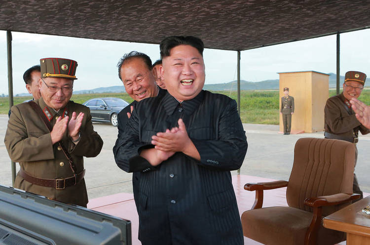 Kim Jong Un celebrates what was said to be the test launch of an intermediate range Hwasong-12 missile.(KCNA/Korea News Service/AP)