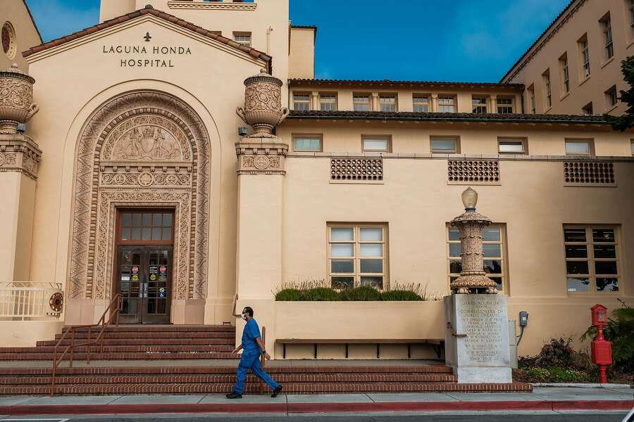Hospital personnel walks past the front of Laguna Honda Hospital in San Francisco, Calif. on Tuesday March 31, 2020.