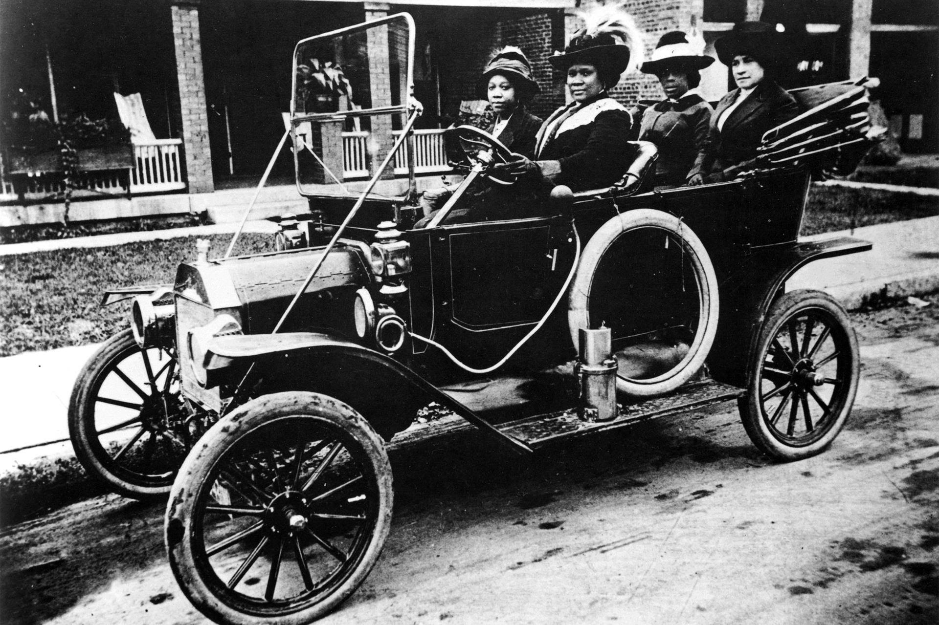 Madam C. J. Walker and companions in her Waverley electric automobile on West Street in Indianapolis in the 1910s.