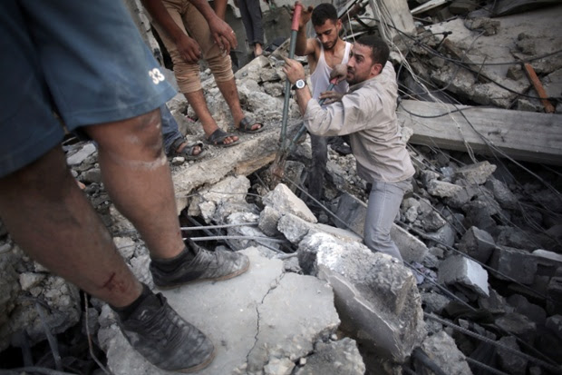 Palestinians search the rubble of a destroyed house where five members of the Ghannam family were killed in an Israeli missile strike early morning in Rafah refugee camp, southern Gaza Strip.