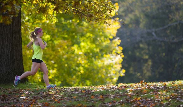 A female runner in bright clothing in a forested area