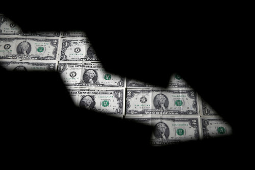 FILE PHOTO: Dollar banknotes are seen through printed stock graph in...