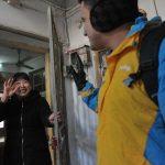 Une étudiant étranger embauché comme livreur par Suning, le spécialiste chinois du e-commerce pour le Nouvel an chinois, sur le seuil d'une cliente à Nankin, dans l'Est chinois, le 30 janvier 2016. (Crédits : Wu jun / Imaginechina / via AFP)