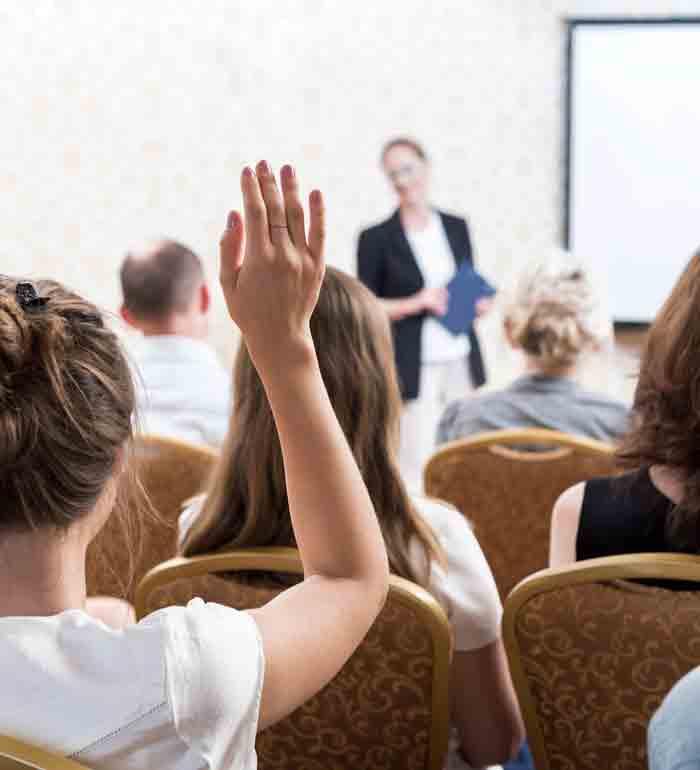 woman raising hand during presentation
