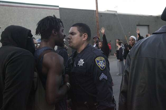 "A police officer and a protester have a tense moment before a scuffle breaks out between a different protester and police officers near the port during an ""F the Police"" march held in solidarity with Ferguson, Mo., where there was a fatal shooting of an unarmed 18-year-old black man earlier in the week August 15, 2014 in Oakland, Calif. Photo: Leah Millis, The Chronicle"