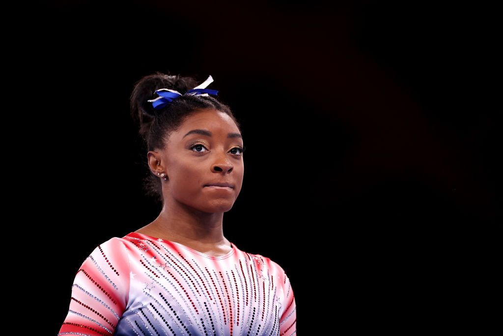 A black athlete with a red suit and a blue ribbon in her black hair.