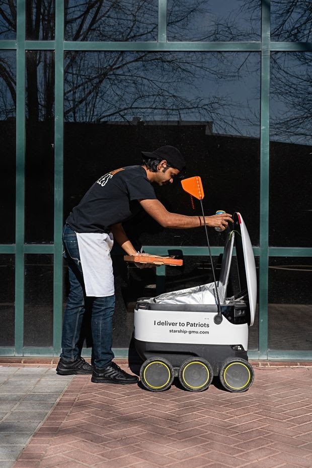 Abhishek Khandkar of Blaze Pizza at George Mason University in Fairfax, Va., loads up a delivery robot built by Starship Technologies that makes deliveries autonomously across campus.