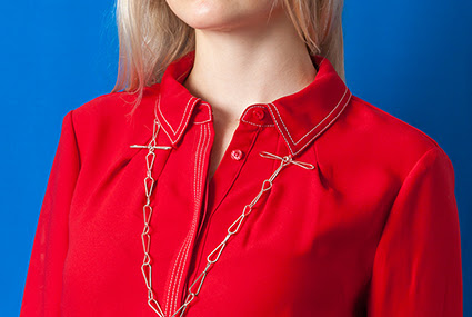 A photograph of a model in a red jumpsuit against a bright blue background. They are wearing a long silver necklace by Sally Cuthbert.
