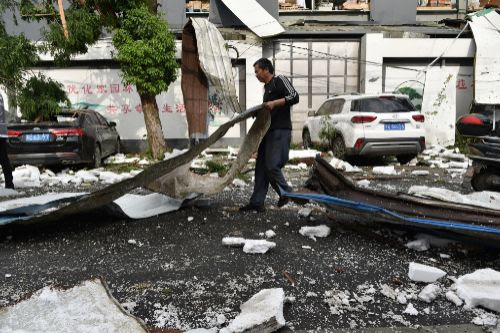 Suzhou (China).- A villager clears the road of debris in the aftermath...