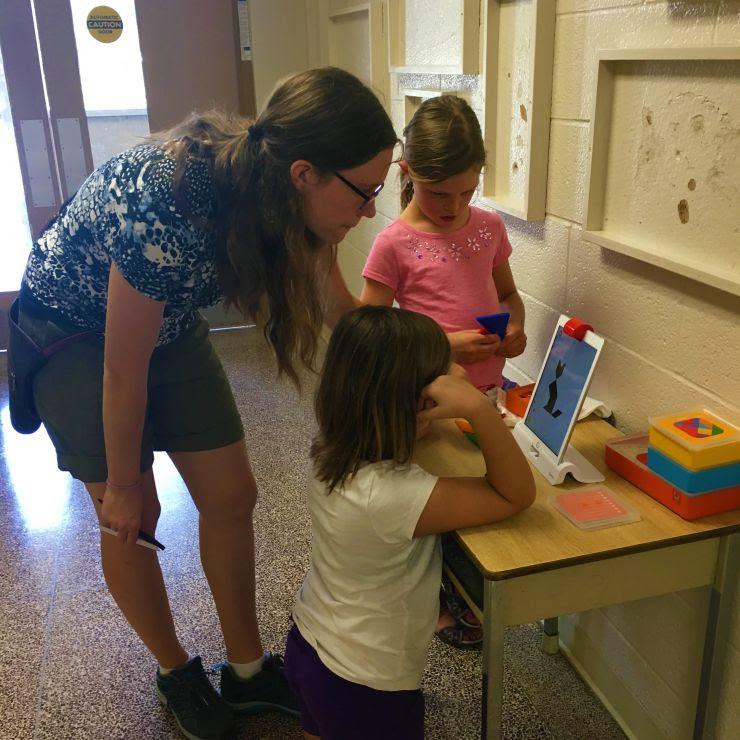 Students doing math on an iPad with a teacher
