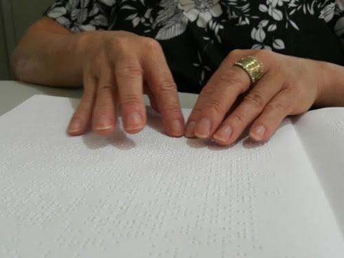 Muher com deficiência visual lê livro em Braille em biblioteca de Taguatinga, no Distrito Federal