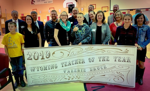 "Mrs. Bruce stands with faculty and students from her school behind a banner that reads, ""2019 Wyoming Teacher of the Year, Valerie Bruce."""