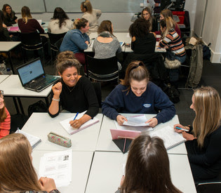 Image of students having group discussions in a seminar room.