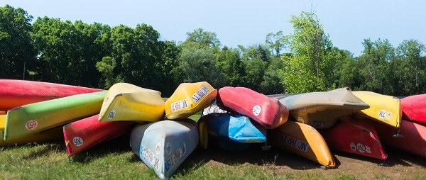 a pile of colorful canoes, upside down, on the grass, blue sky behind