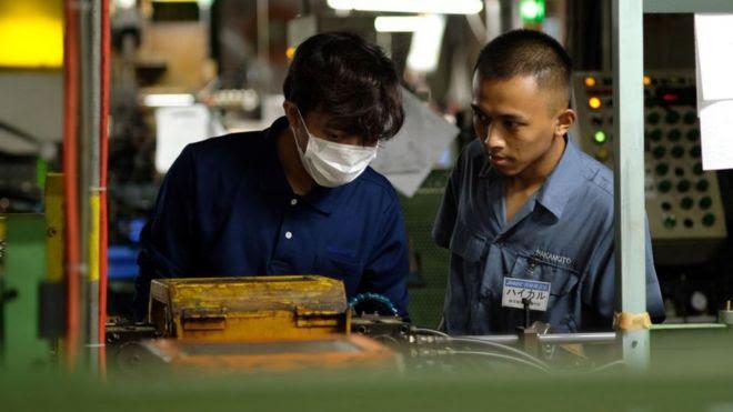 Trablhadores lado a lado em fábrica