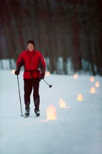 man cross-country skiing by candlelight
