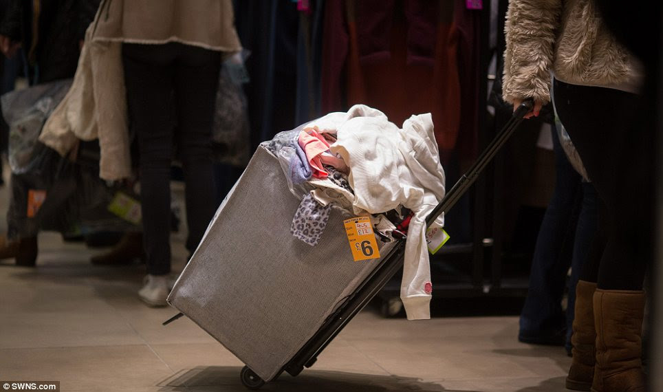 Overflowing: A shopping bag in Cheltenham full of clothes many of which were discounted by 50 per cent