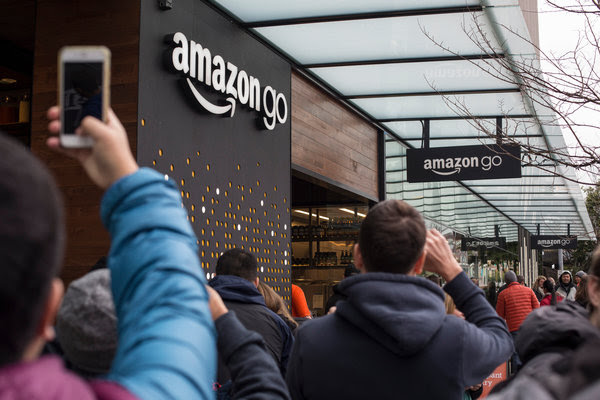 Shoppers and passers-by glimpsed the exterior of the Amazon Go grocery store during the location's beta launch in Seattle in December.