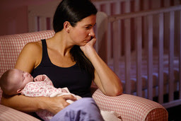 Frustrated mother holding her sleeping baby.