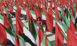 A girl walks inside a cluster of UAE flags.