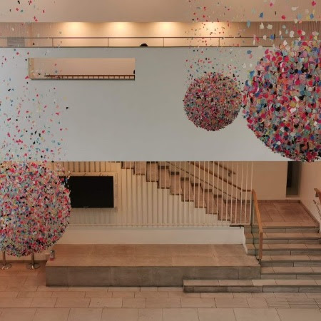 Three globe-like installations made of colourful waste polythene hanging in Gallery Square by artist Claire Morgan
