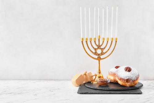 Menorah_ dreidels and donuts for Hanukkah on white background
