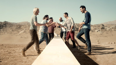 Two groups of young men, bi-cultural Hispanics from the U.S. and Mexicans from Mexico, come together over the wall, the structure is revealed to be three-feet tall, the perfect height for a group of friends to rest their Tecate's on.